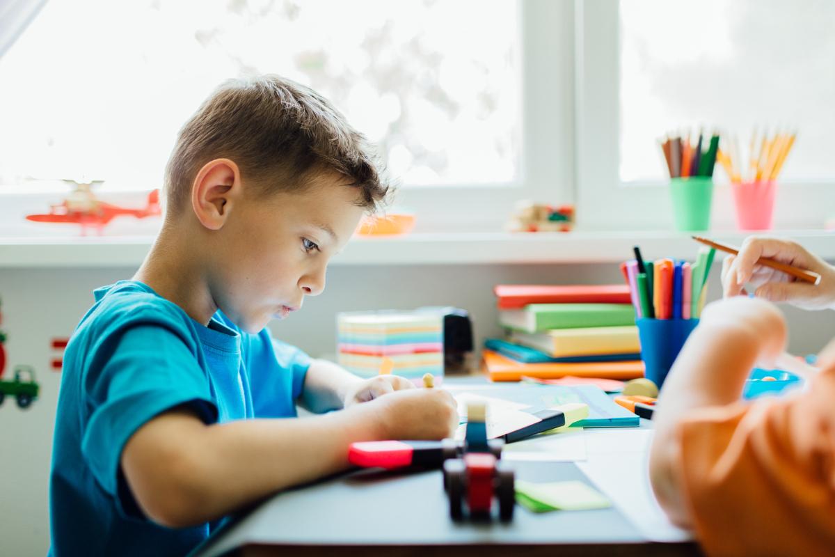 Vista lateral de un estudiante silbando haciendo su tarea
